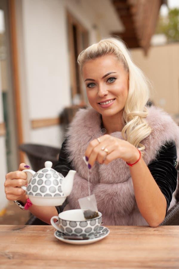Beau thé de boissons de jeune femme sur le terace de barre en automne tôt photographie stock libre de droits