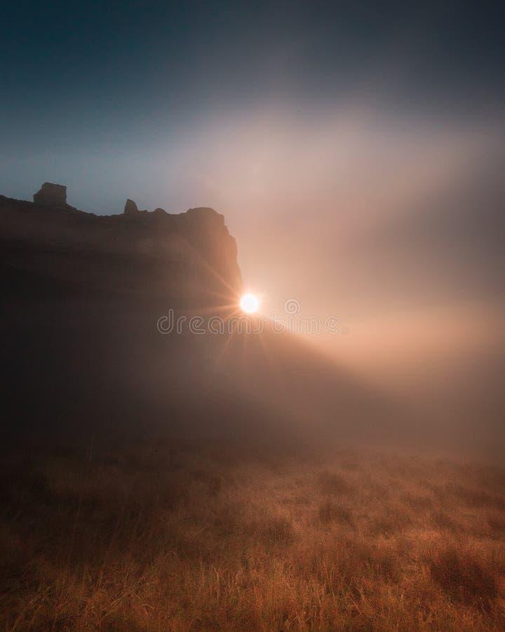 Beau tir de champ brumeux de désert avec de hautes roches le soir avec le soleil brillant  photographie stock libre de droits