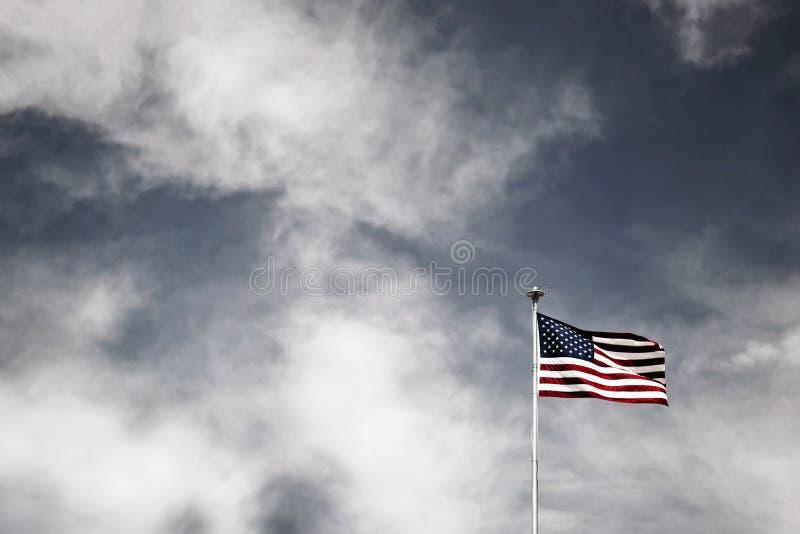 Beau tir du drapeau américain de ondulation sur un poteau blanc avec stupéfier le ciel nuageux à l'arrière-plan images libres de droits