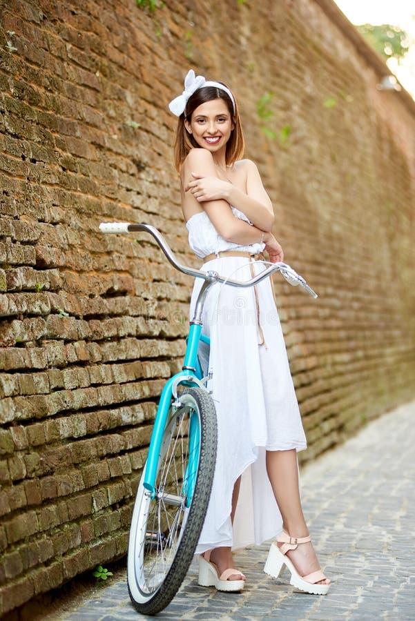 Beau vélo heureux d'équitation de femme dans la ville image stock