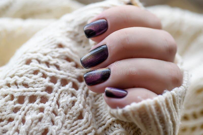 Beau vernis à ongles à disposition, manucure pourpre d'art d'ongle, fond blanc photos stock
