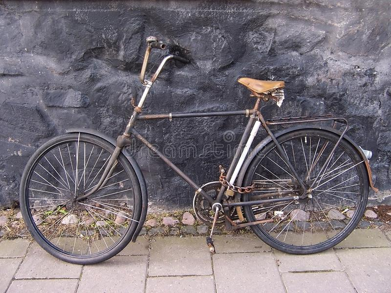 Beau vieux, cru et rétro bicyclette, datant from 1950 s'est garé dans le passage entre de vieilles maisons fixées avec la chaîne  image stock