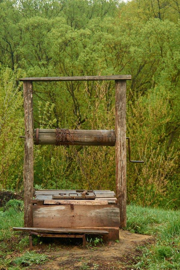 Beau vieux puits en bois dans le village à l'arrière-plan image libre de droits