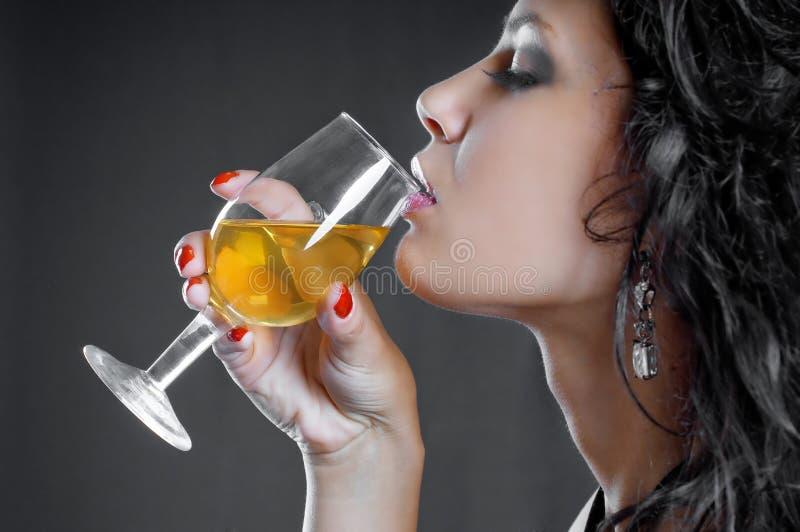 Beau vin de boissons de fille sur le noir photographie stock libre de droits