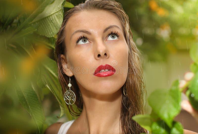 Beau visage blond de femme sous la pluie en automne avec le fond vert en parc image libre de droits