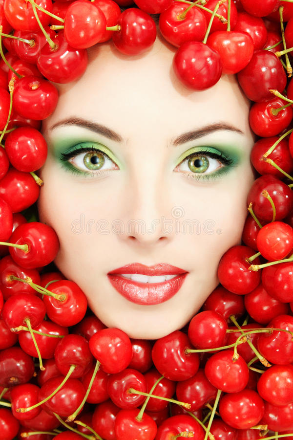 Beau visage de femme avec la cerise fraîche mûre rouge photo stock