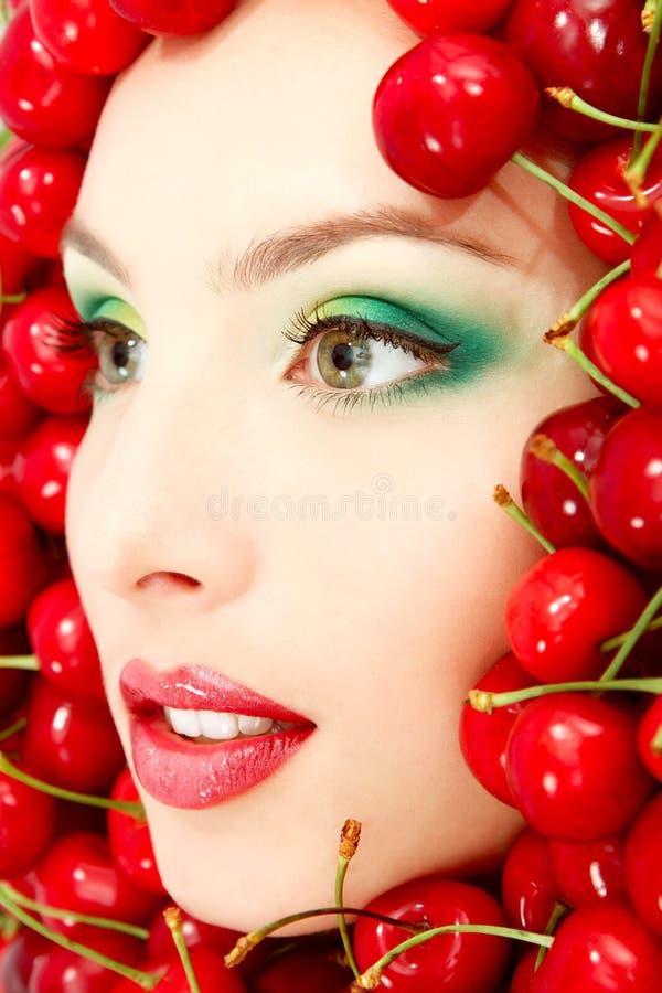 Beau visage de femme avec la grande cerise fraîche mûre rouge image libre de droits