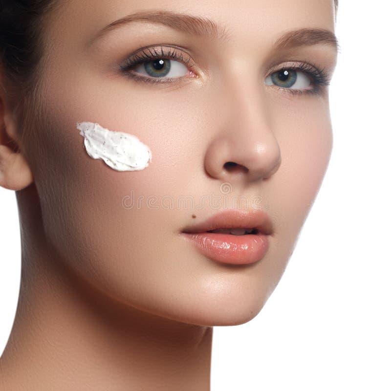 Beau visage de jeune femme avec de la crème cosmétique sur une joue Concept de soin de peau Portrait de plan rapproché d'isolemen photos stock