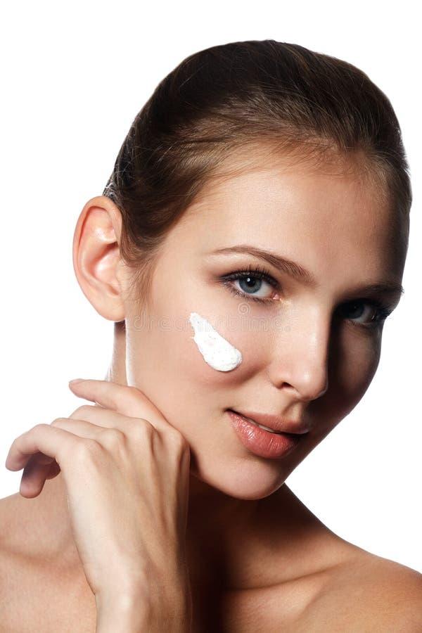 Beau visage de jeune femme avec de la crème cosmétique sur une joue La SK image stock