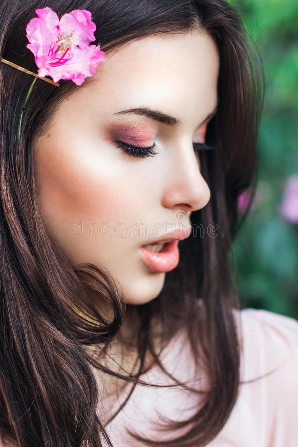 Beau visage de jeune femme avec le maquillage au-dessus des fleurs roses Portrait de la fille assez en bonne santé de peau extéri image libre de droits