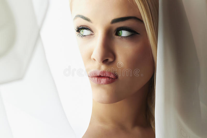 Beau visage de jeune femme blonde de jeune mariée. Regard de fille dans le voile de Window.Bridal. Rideaux photos libres de droits