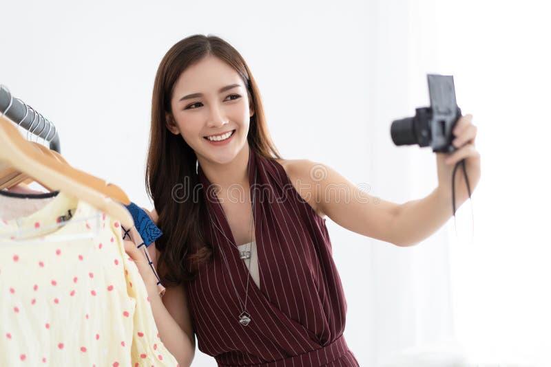Beau vlogger élégant de sourire asiatique de mode de fille choisissant l'habillement dans le magasin d'habillement se tenant avec photos libres de droits