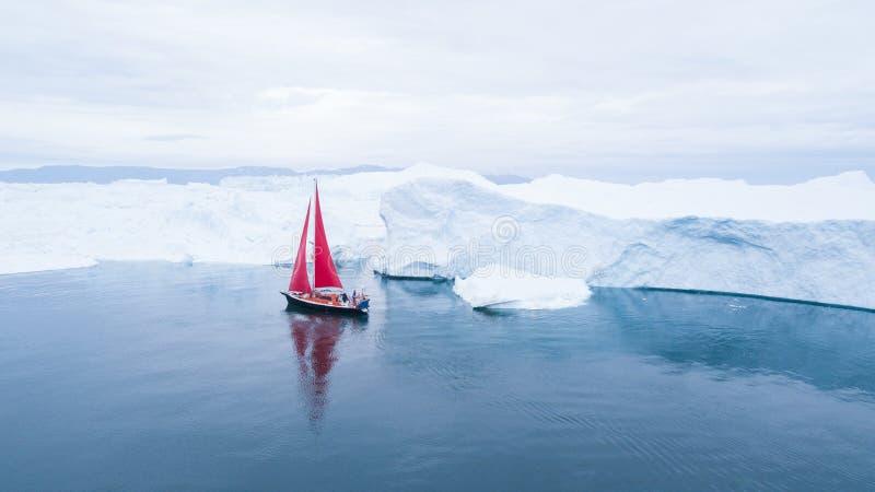 Beau voilier rouge à côté d'un iceberg massif image libre de droits