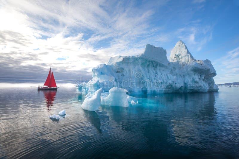 Beau voilier rouge à côté d'un iceberg massif photographie stock libre de droits