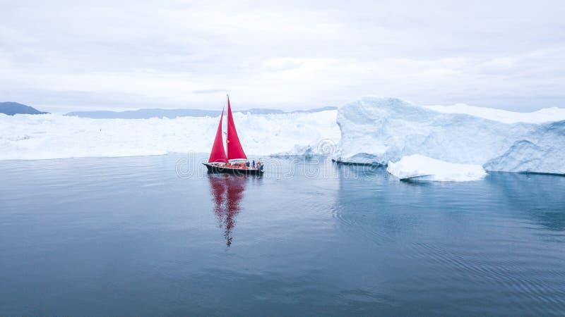 Beau voilier rouge à côté d'un iceberg massif photo stock