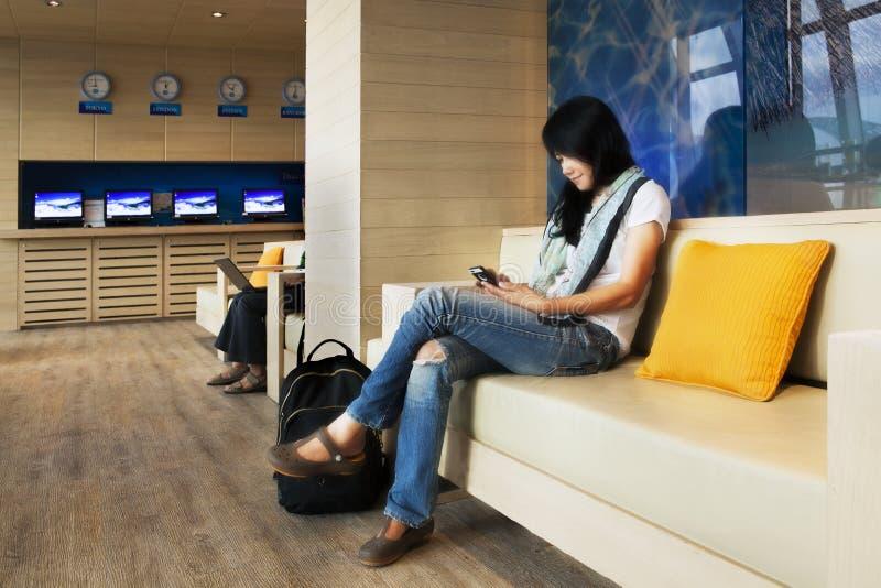 Beau voyageur avec le téléphone portable dans l'aéroport. image stock