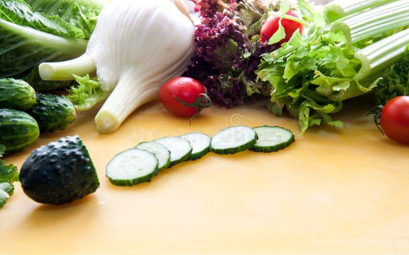 Beaucoup assortiment des verts, de la laitue et des légumes sur un conseil jaune avec le concombre coupé en tranches au centre image stock
