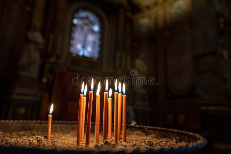 Beaucoup bougies brûlantes avec la profondeur du champ dans un chandelier de grès dans une église avec un crucifix dans photographie stock