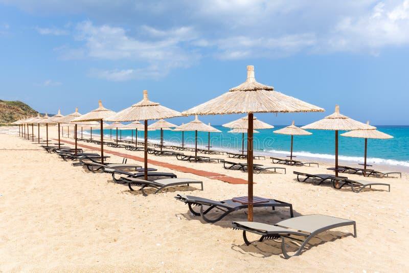 Beaucoup couvrent de chaume des parapluies de plage sur la plage près de la mer photographie stock libre de droits