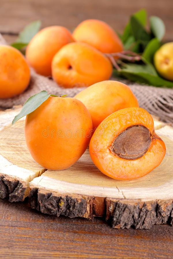 Beaucoup d'abricot frais et m?r dans un sac sur un fond en bois brun image libre de droits