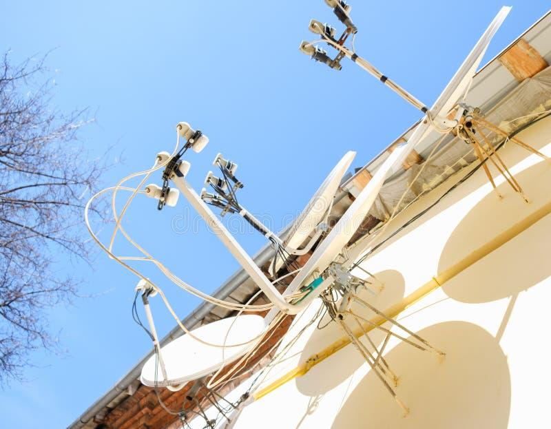 Beaucoup d'antennes paraboliques montées sur le mur image libre de droits
