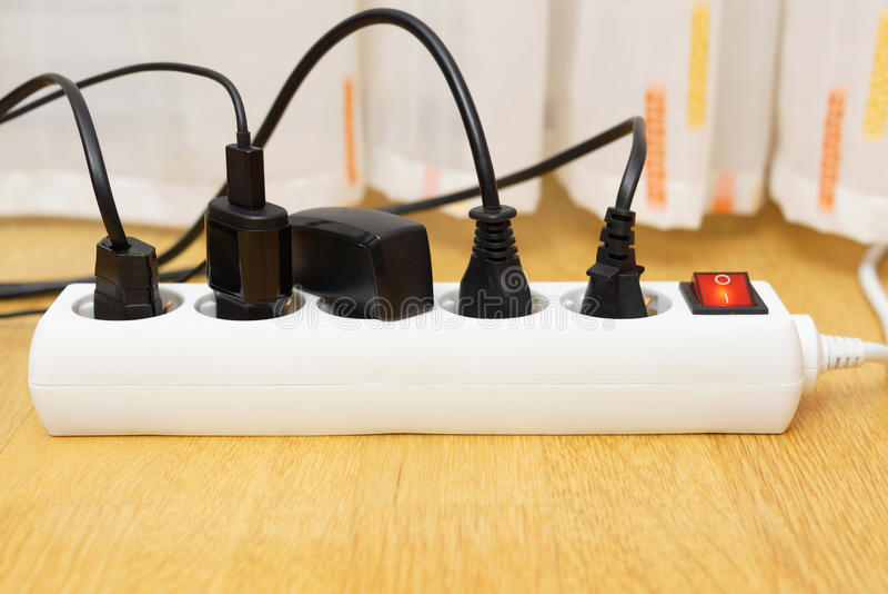 Beaucoup d'appareils électriques pluged dans le protecteur de montée subite Le contre de puissance images libres de droits