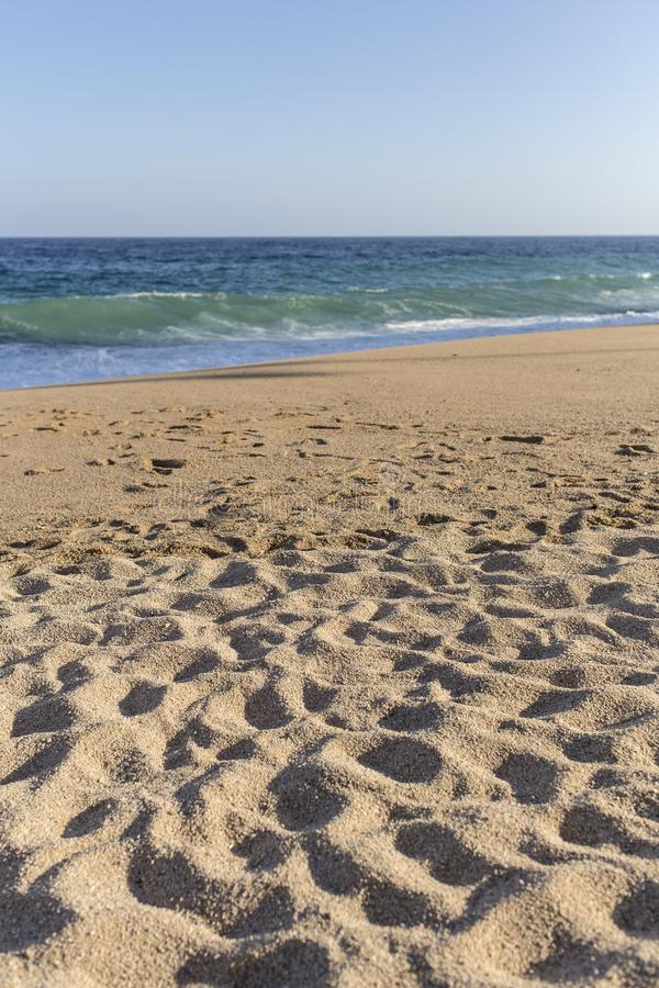 Beaucoup d'empreintes de pas o un sable de plage avec de l'eau tranquille en Costa Brava photos stock