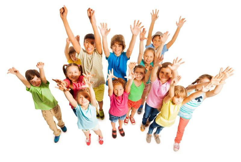 Beaucoup d'enfants se tiennent d'isolement sur le blanc dans le grand groupe images stock