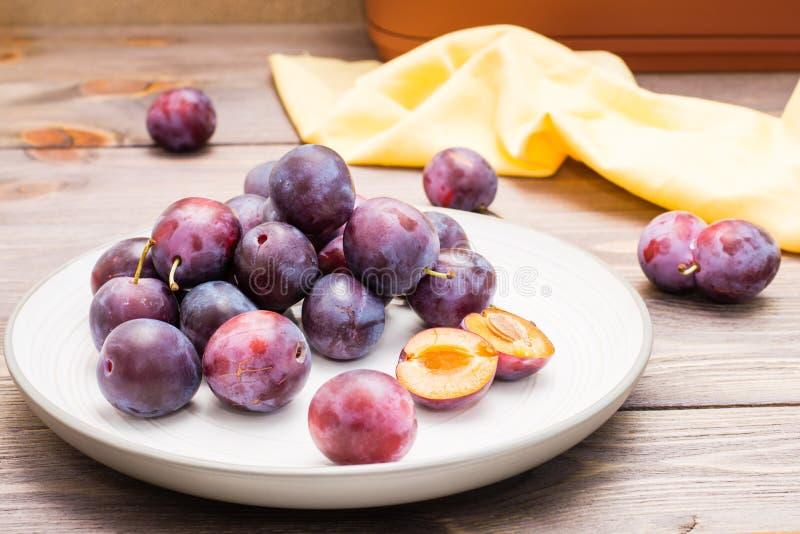 Beaucoup de baies mûres entières de prune bleue et d'une ont bissecté la baie images libres de droits