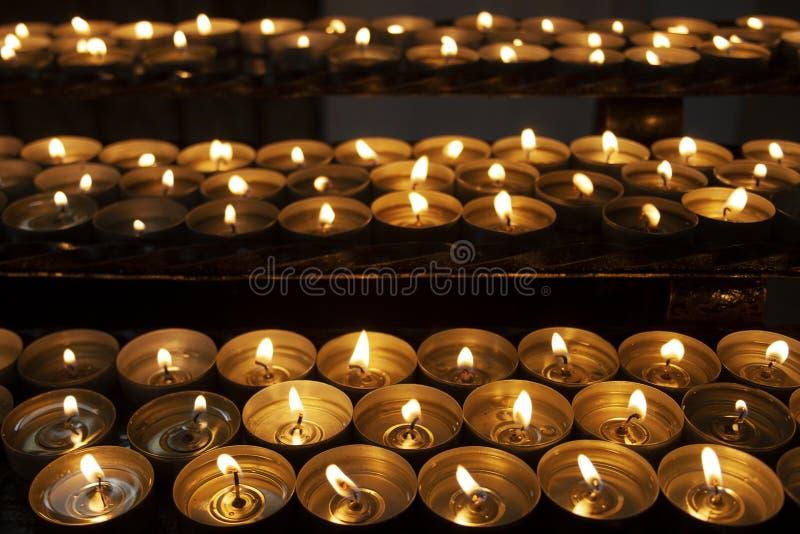 Beaucoup de belles bougies allumées dans une rangée rougeoyant avec une lumière jaune d'or photo libre de droits