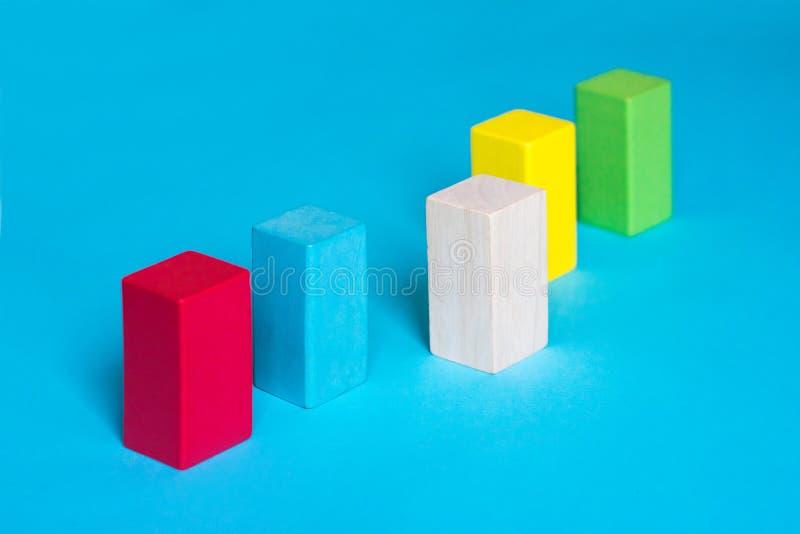 Beaucoup de blocs colorés dans une rangée et un bloc en bois sur le fond bleu Choix, différence, prise de décision, concept d'ass photographie stock libre de droits