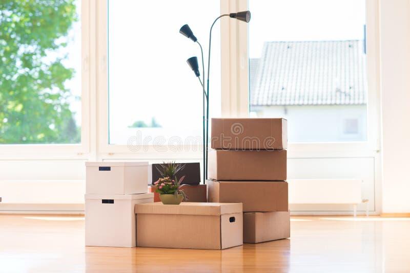 Beaucoup de boîtes en carton dans la maison lumineuse pendant la relocalisation photographie stock libre de droits