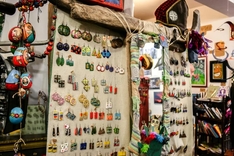 Beaucoup de boucles d'oreille multicolores accrochant contre la toile de toile, un miroir et d'autres bibelots dans le magasin av photo stock