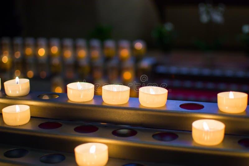 Beaucoup de bougies brûlantes avec la profondeur du champ et du fond defocused photographie stock libre de droits