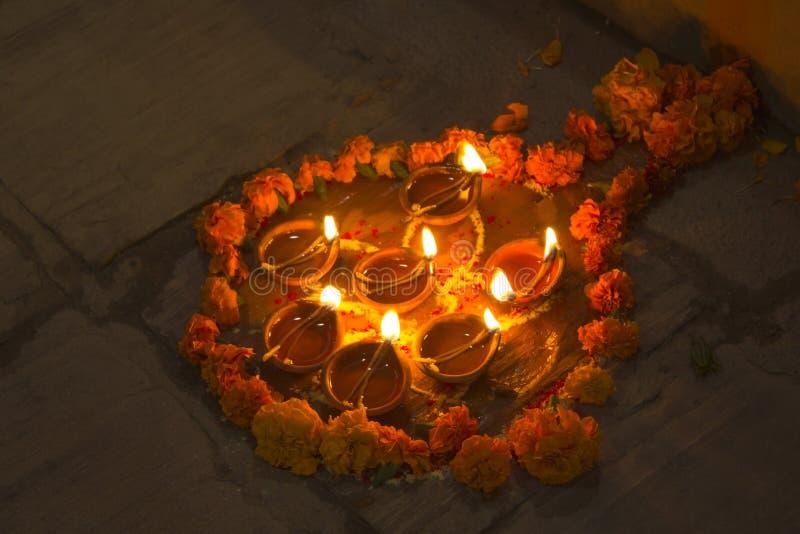 Beaucoup de bougies brûlantes d'huile en cercle des fleurs fraîches sur la rue à la nuit de Diwali photographie stock