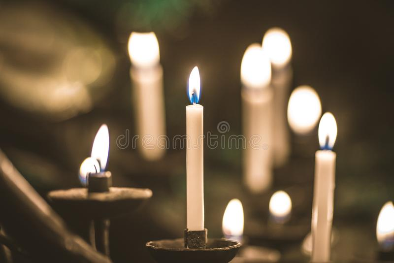 Beaucoup de bougies jaunes de cire brûlante d'église dans grand sur un support spécial photographie stock