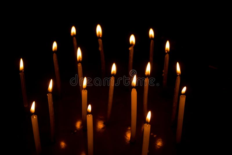 Beaucoup de bougies de Noël brûlant la nuit sur le fond noir photographie stock libre de droits
