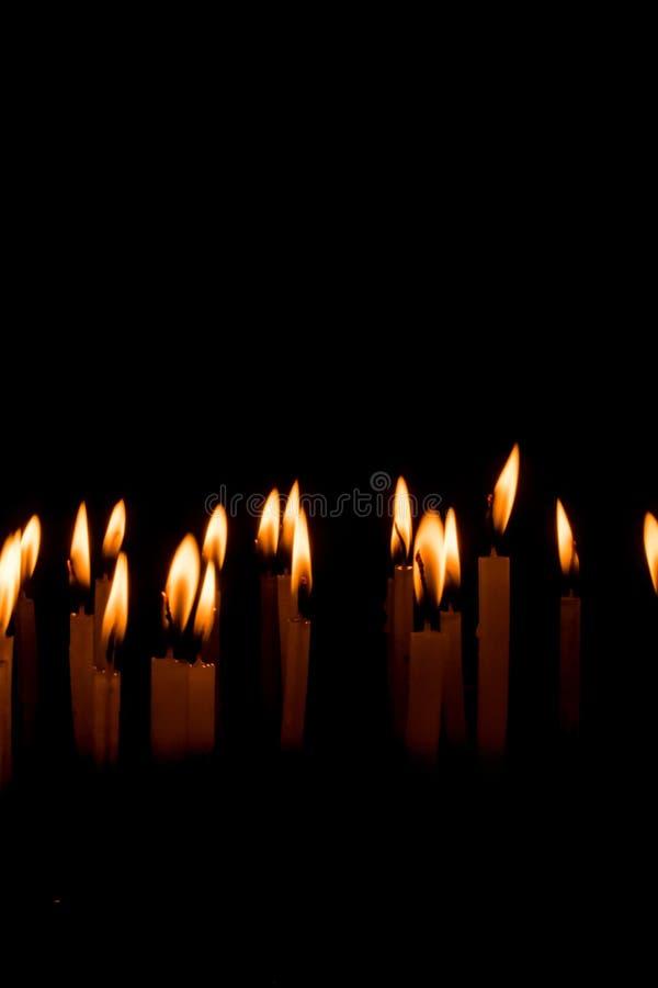 Beaucoup de bougies de Noël brûlant la nuit sur le fond noir photos libres de droits