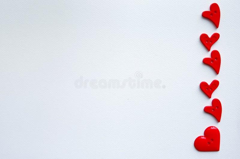 Beaucoup de boutons de forme de coeur disposés sur le papier image stock