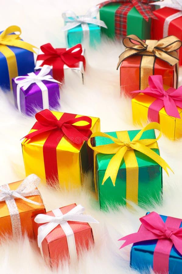 Beaucoup de cadeaux sur la fourrure fausse blanche. (verticale) photographie stock libre de droits