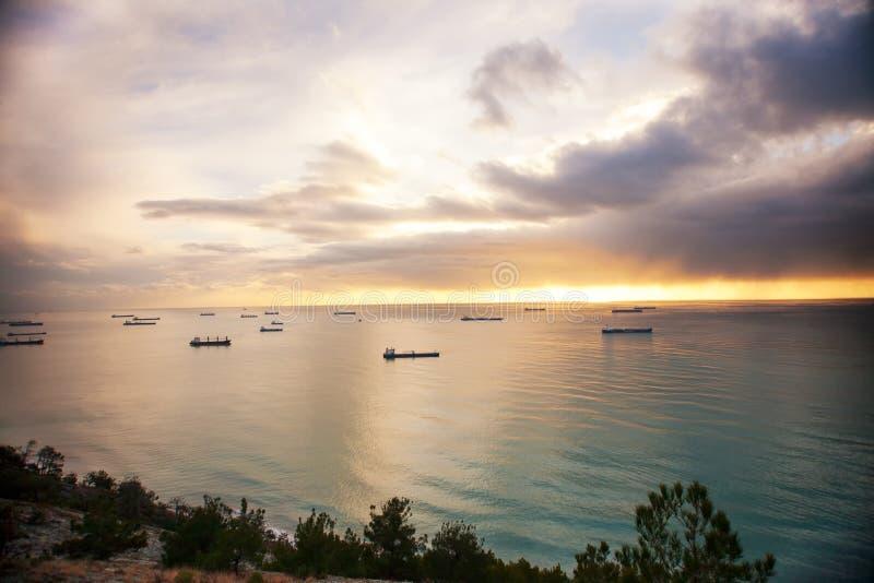 Beaucoup de cargos attendant l'entrée de port Coucher du soleil coloré au-dessus de mer photo libre de droits