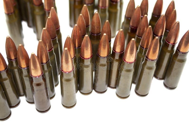 Beaucoup de cartouches debout pour le fusil d'assaut de kalachnikov d'isolement sur le fond blanc photo libre de droits