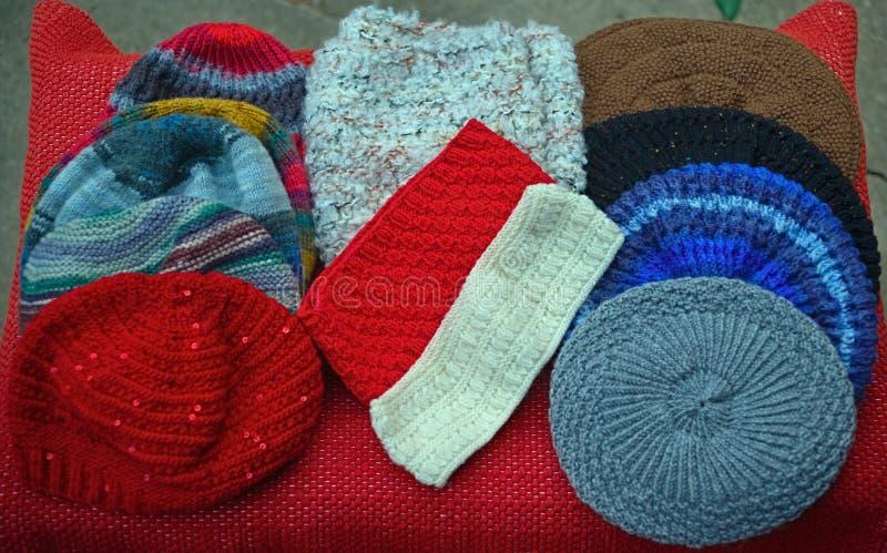 Beaucoup de chapeaux traditionnels faits main colorés d'hiver sur la table photos stock