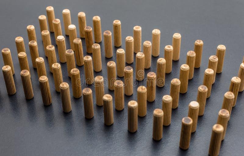 Beaucoup de chevilles en bois se tenant verticalement sur un fond noir photographie stock libre de droits