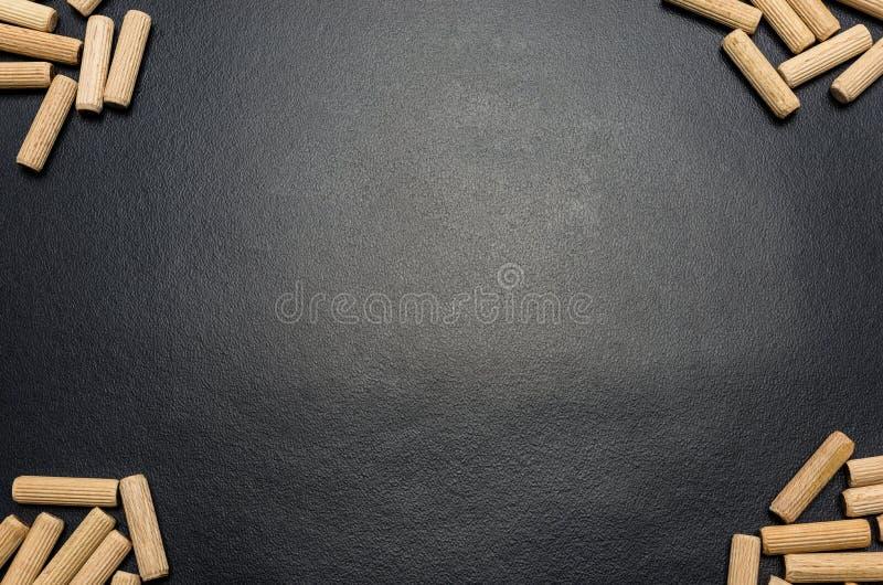 Beaucoup de chevilles en bois se trouvant à plat sur un fond noir photographie stock