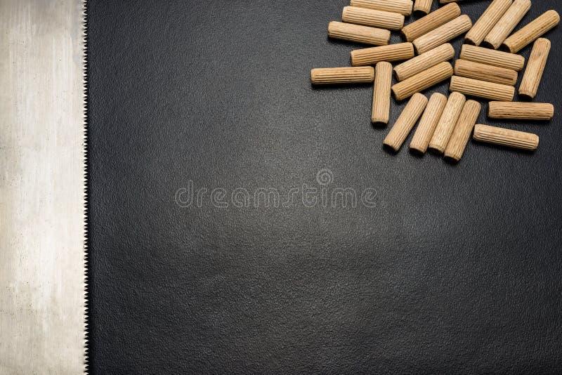 Beaucoup de chevilles et scie en bois de main pour le bois se trouvant à plat sur un fond noir photo libre de droits