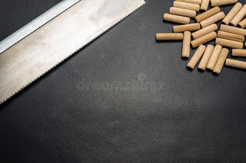 Beaucoup de chevilles et scie en bois de main pour le bois se trouvant à plat sur un fond noir photos libres de droits