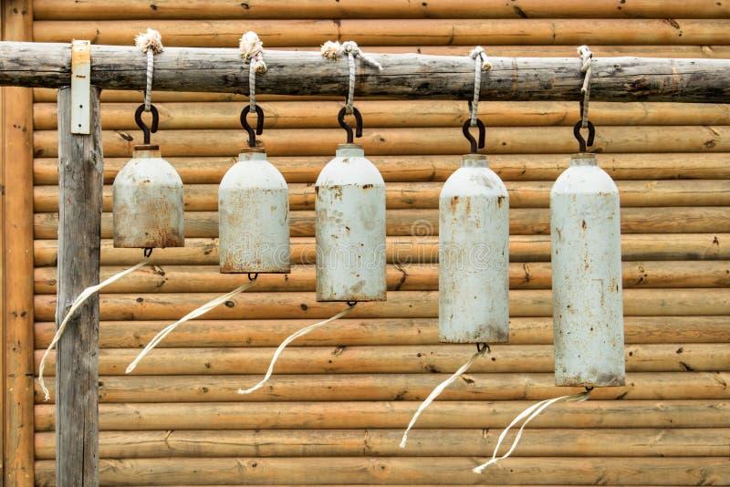 Beaucoup de cloches d'église modernes accrochant dehors sur le fond d'un mur en bois photos stock
