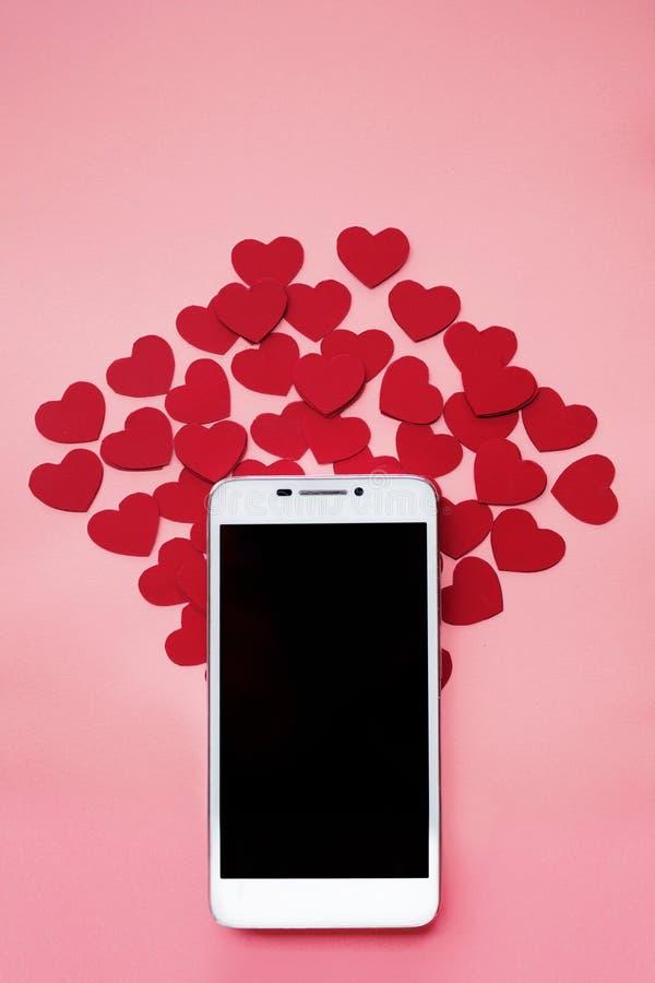 Beaucoup de coeurs et smartphone Le concept à aimer dans les réseaux ou l'APP sociaux de dater Fond rose image stock