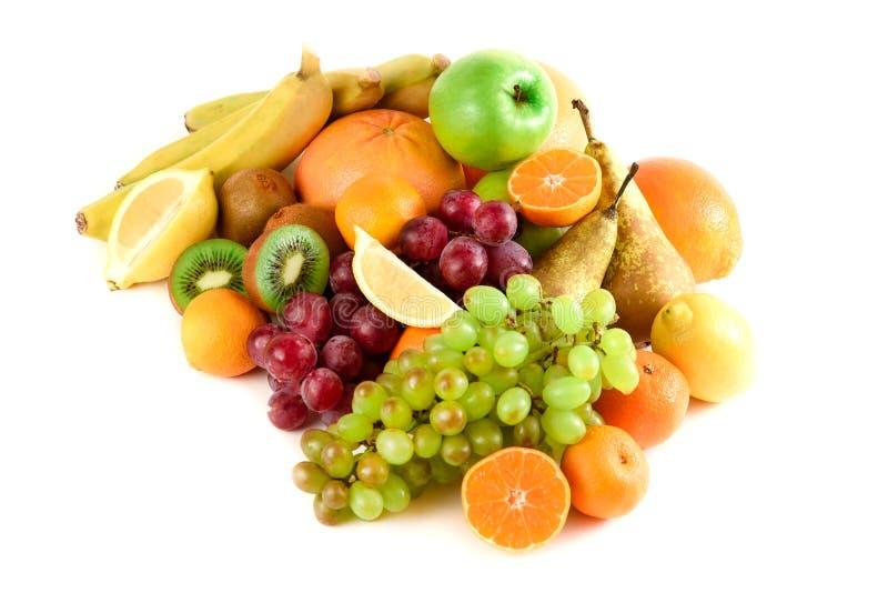 Beaucoup de colorés, lumineux, fruit frais sur un fond blanc Kiwi, pamplemousses, bananes, raisins, citron, mandarines, oranges image libre de droits